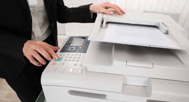 hand pushing the green button on a multifunction copier