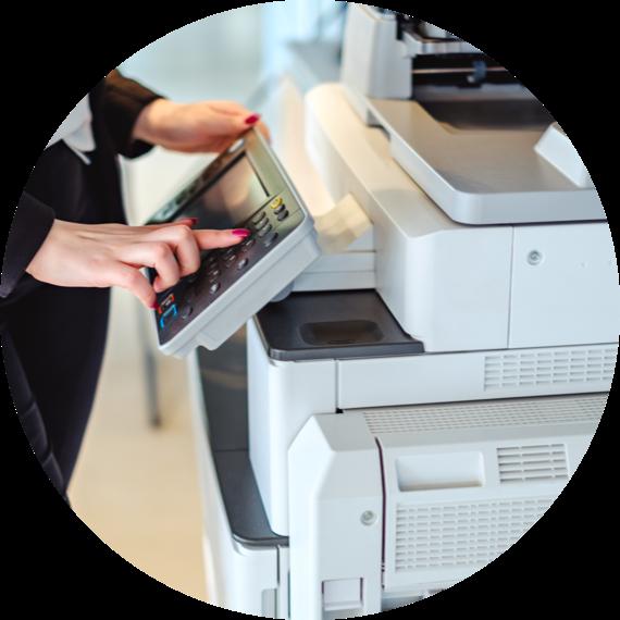 a woman's hand pressing a button of a copier machine