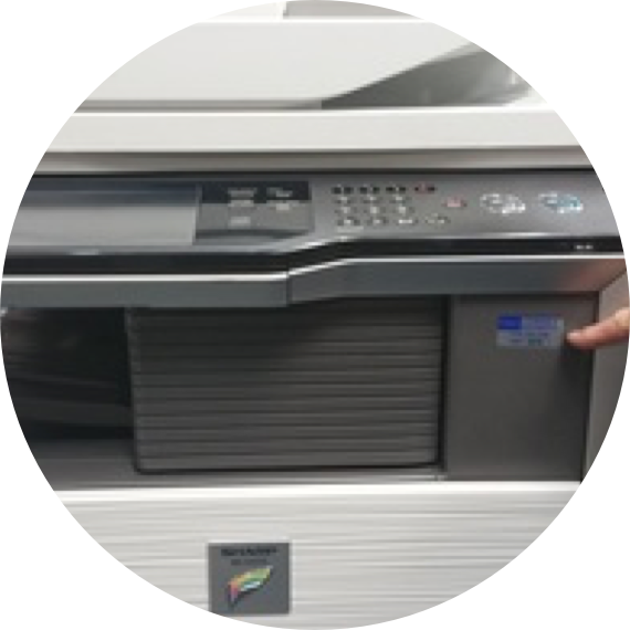 a finger pointing to the logo on a printer machine.